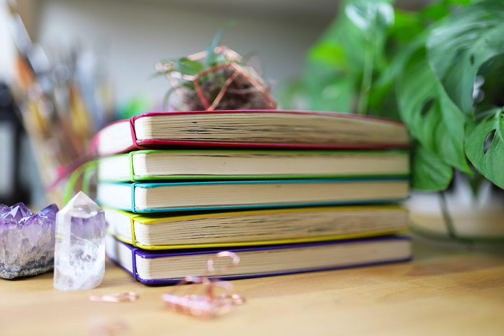 Five colorful journals stacked on top of one another.