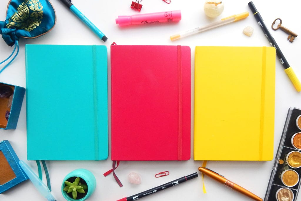Three colorful journals laid out on desk with art supplies around them.