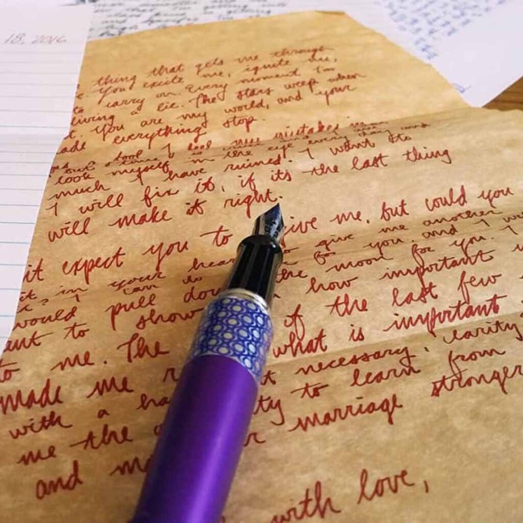 purple fountain pen laying on paper with handwritten words