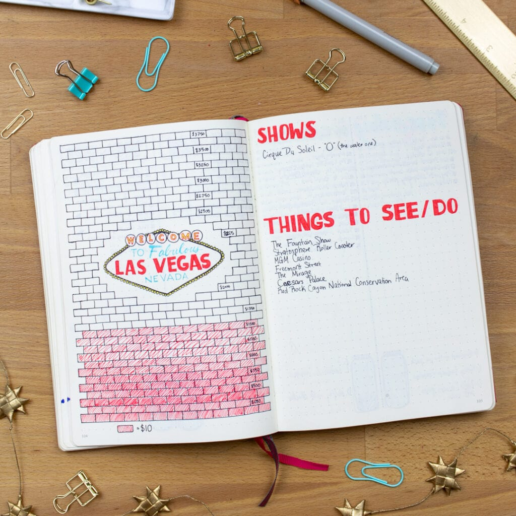 An overhead view of a savings tracker in a bullet journal. The left page is the tracker, partially filled in. The right page is a list of Shows to See and Things to Do.