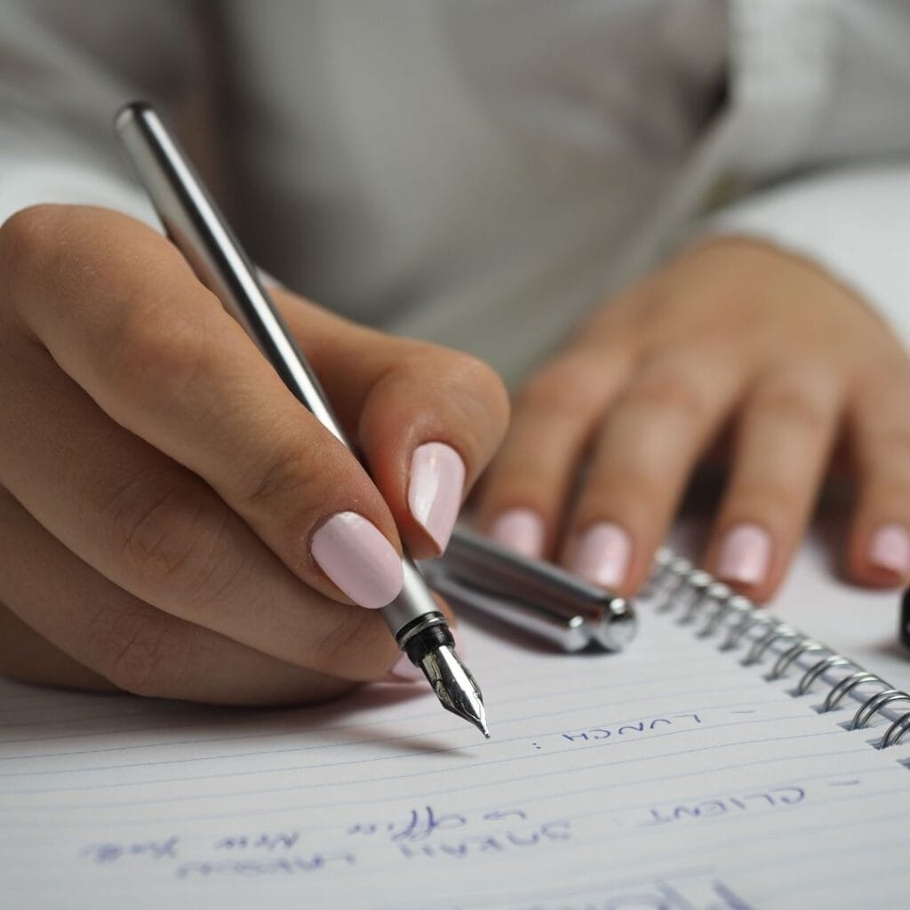 woman's hand writing with a fountain pen