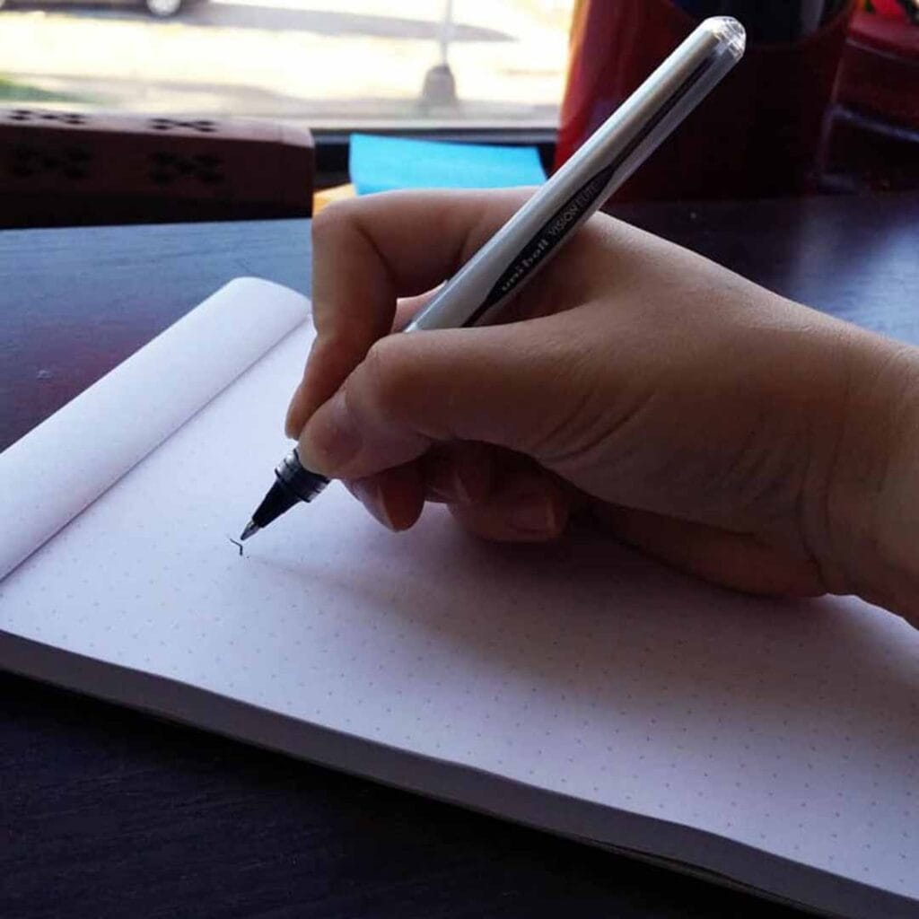 woman's hand gripping a pen tightly