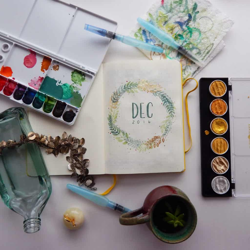 A bullet journal monthly title page, make with a neutral green watercolor paint palette. This image is to demonstrate getting over first-page fear in starting a new notebook.