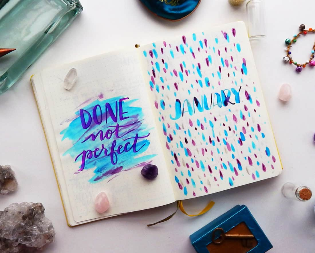A bullet journal monthly title page is open. The left page says 'Done not Perfect; and the right page says 'January'.