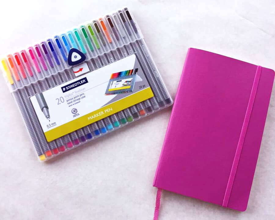 A set of 20 multicolored marker pens and a pink journal sit on top of a table.