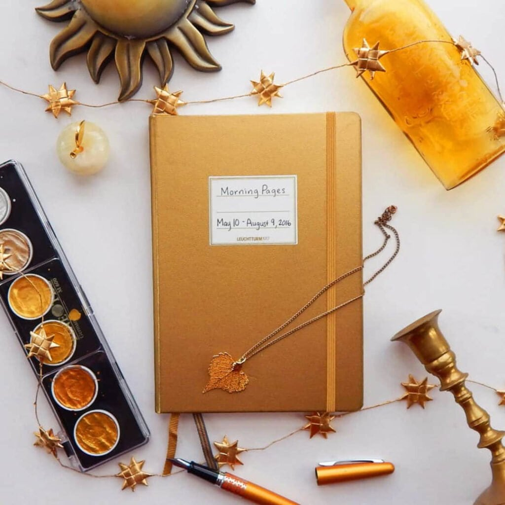 metallic gold bullet journal with paints and gold bottle