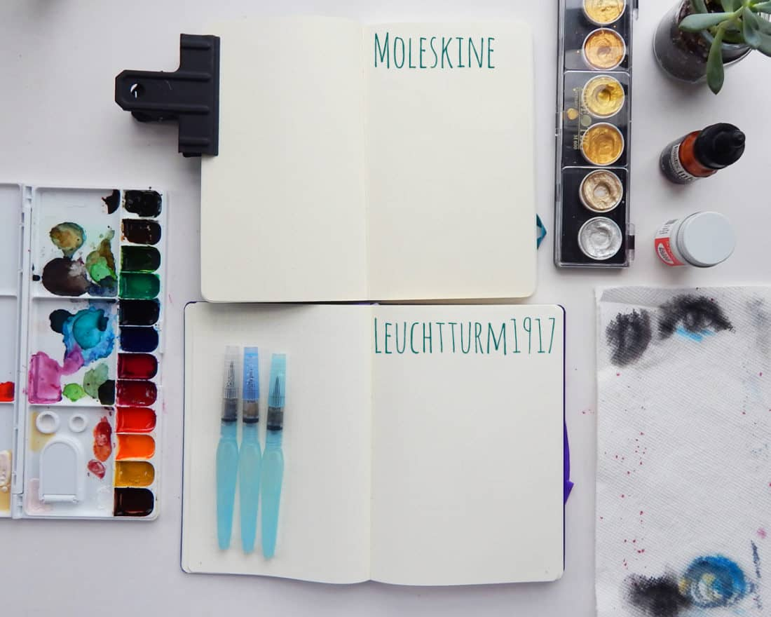 Materials for the article are laid out on a desk. The materials are a watercolor palette, a moleskine journal, a leuchtturm1917 journal, watercolor brush pens, and a metallic watercolor palette.