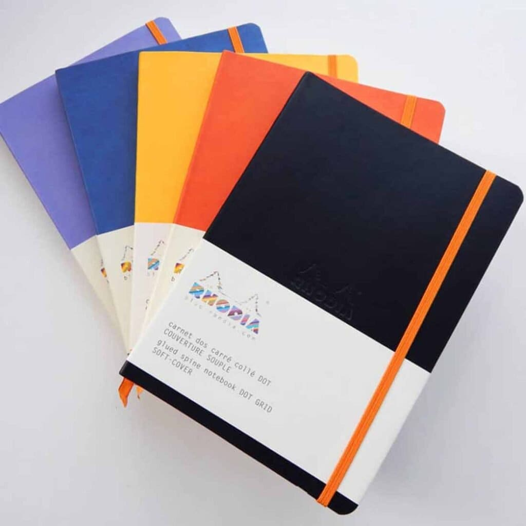 stack of 5 bullet journals in black, orange, yellow, blue and purple
