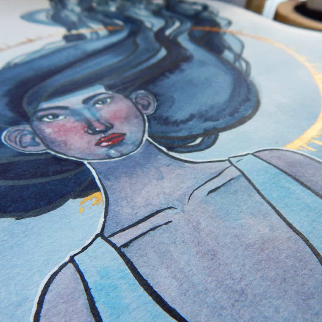 A completed watercolor painting of a woman with a blue color scheme, with gold metallic watercolor details in the background.