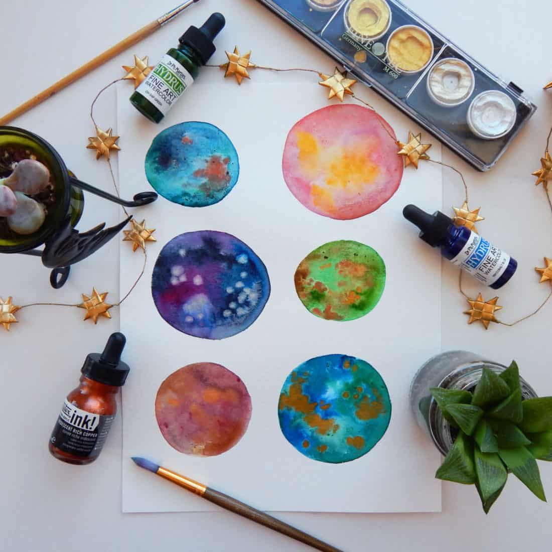 Painting of several planets, created using watercolor paints.