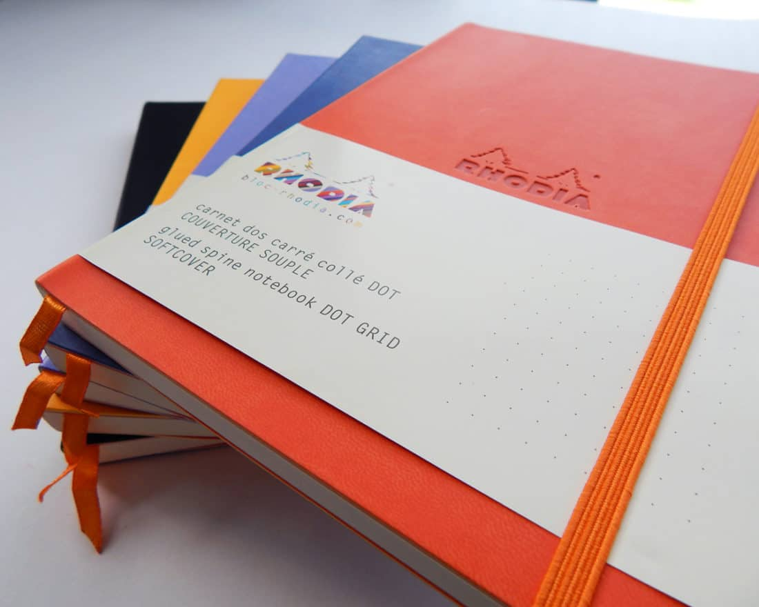 closeup of stack of 5 bullet journals in orange, blue, purple, yellow, and black