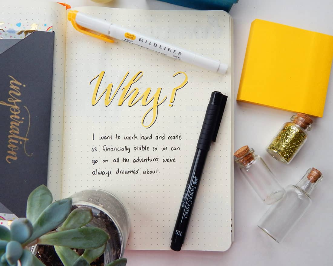 """A bullet journal is open to a page with the following written on it: """"Why? I want to work hard and make us financially stable so we can go on all the adventures we've always dreamed about."""" The image demonstrates the power of having a Why statement for motivation."""
