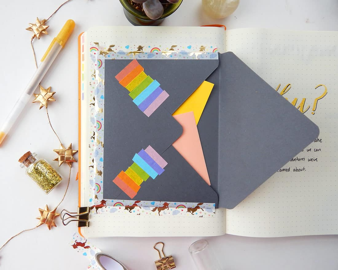 A bullet journal is open to a page that has an envelope attached with washi tape. This image demonstrates having the envelope in your bullet journal to organize loose pieces of paper.