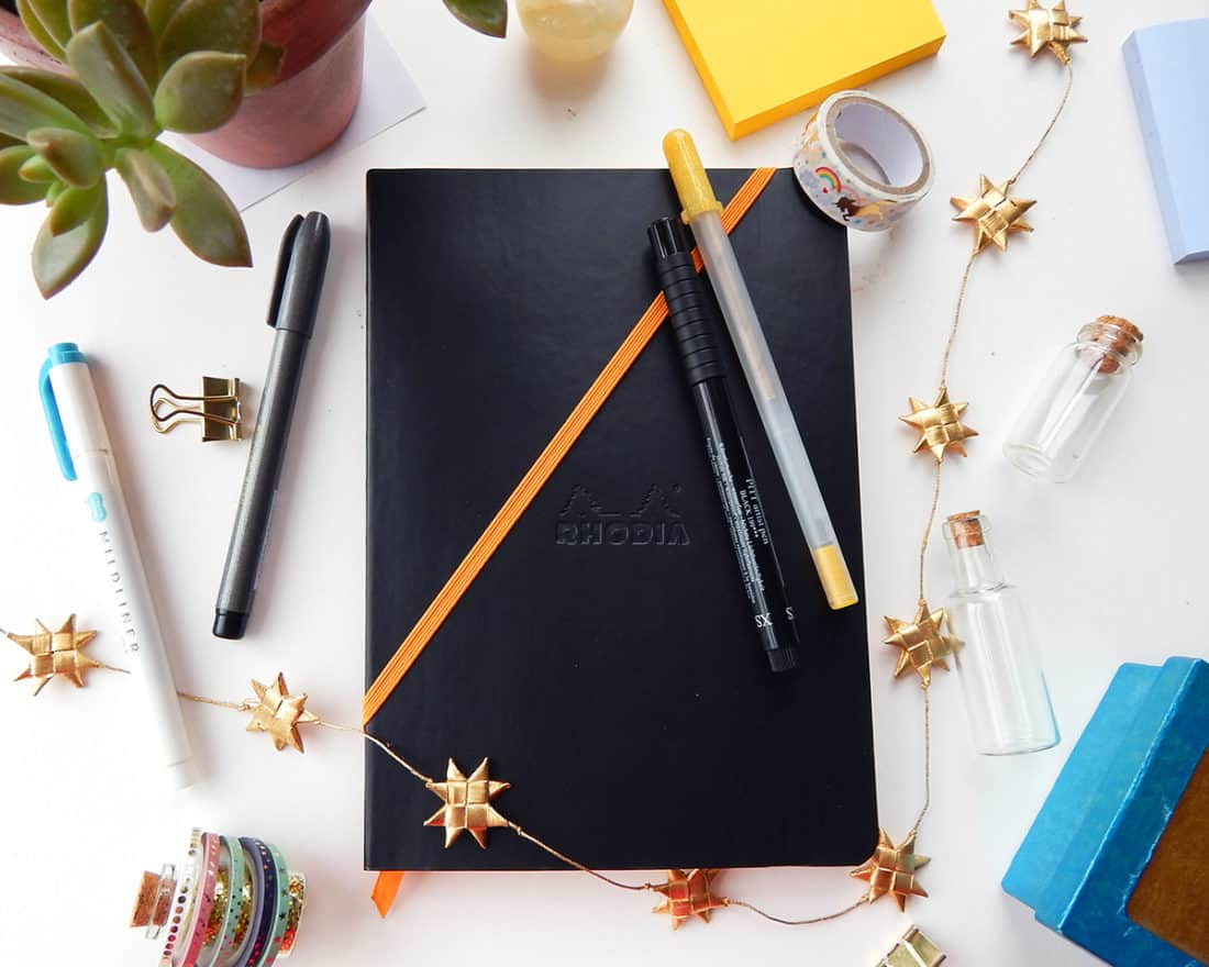 A black bullet journal is closed, with an orange elastic strap wrapped diagonally across the cover. Two pens are hooked onto the elastic strap. This image demonstrates how to use the elastic strap attached to the bullet journal as a way to organize pens.