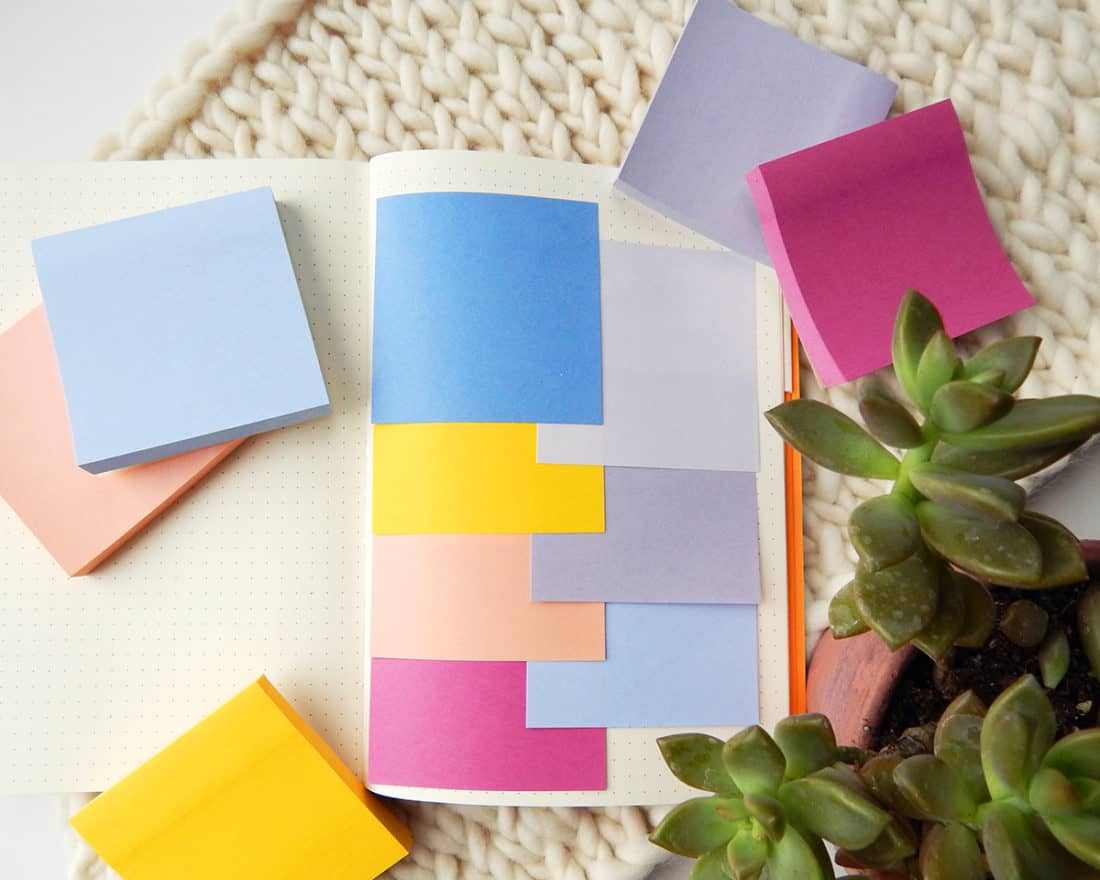 A bullet journal is open, with several blank Post-It notes stuck onto a page. This image demonstrates keeping the Post-It notes readily available to take notes.