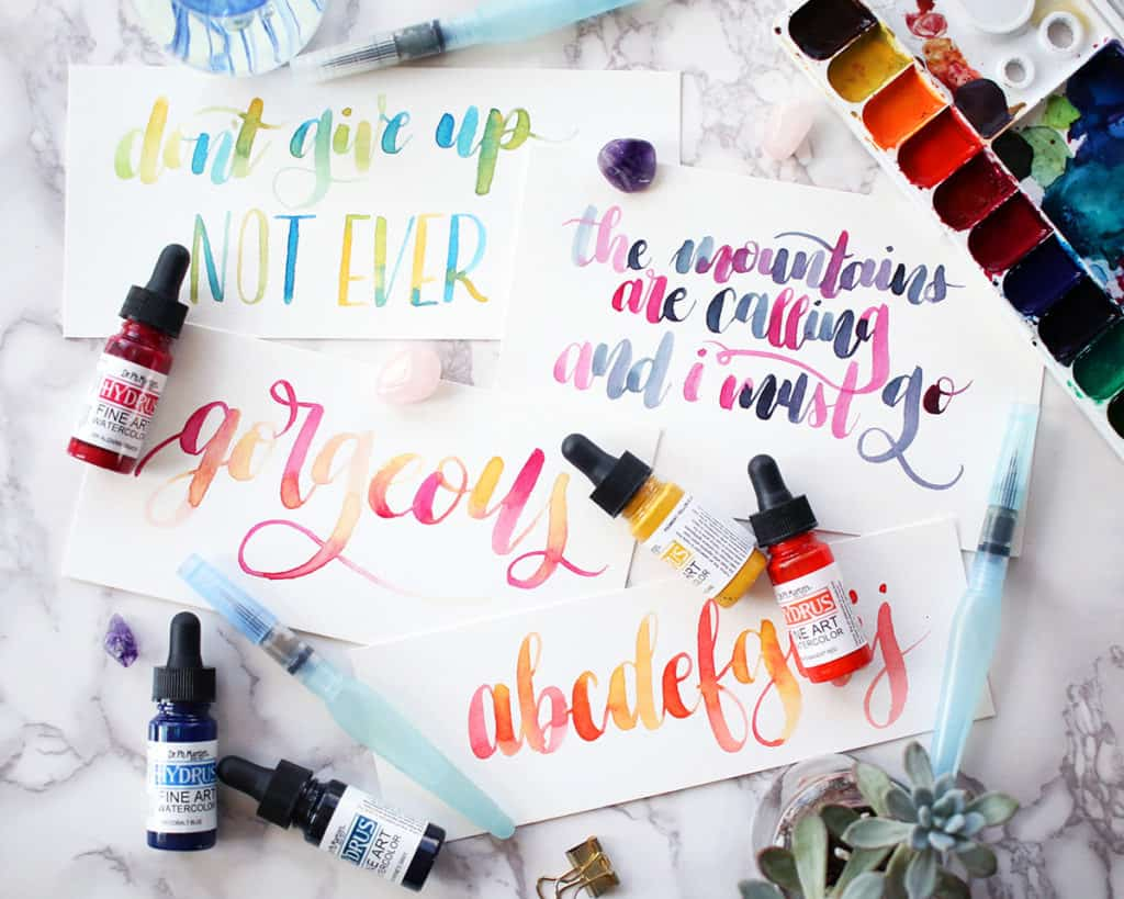 an assortment of pieces of paper with watercolor lettering on them