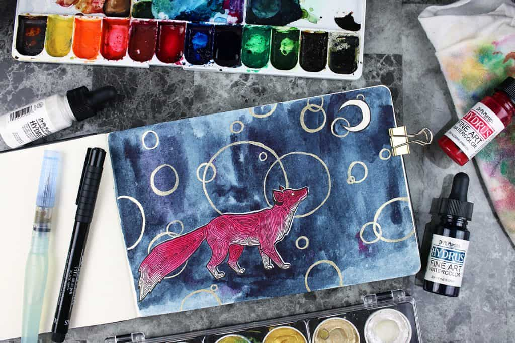A watercolor painting in a watercolor journal. The painting is of a red fox, gazing up at a white moon. The background is navy blue, with a pattern of scattered gold circles.