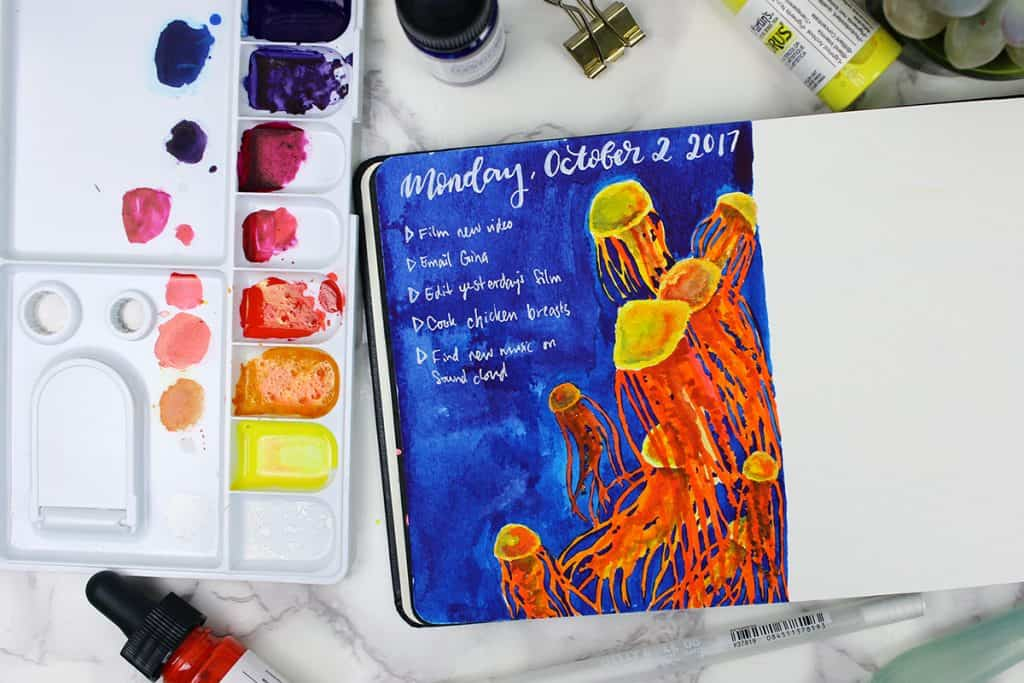 A daily spread in a watercolor bullet journal. The theme is jellyfish, with red and gold jellyfish painted over a blue background.