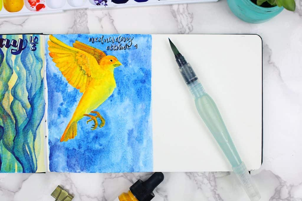 A daily spread in a watercolor bullet journal. The theme of this day is a yellow bird painted on a blue background.