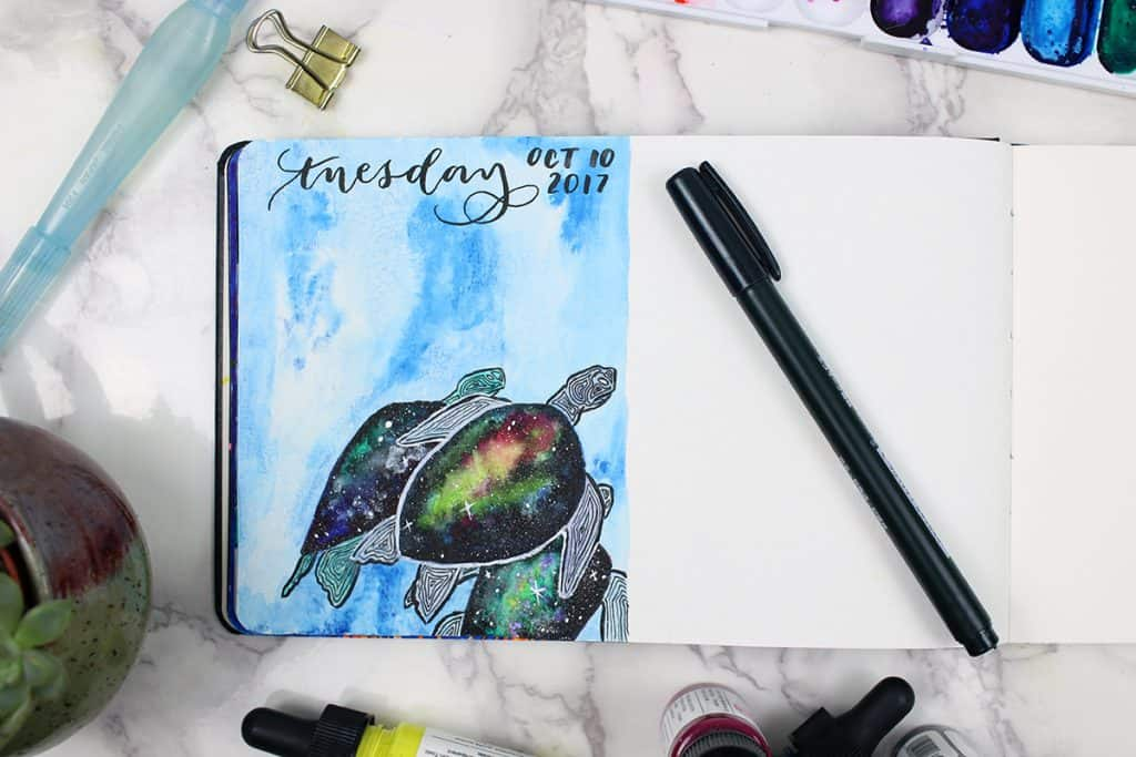 A daily watercolor bullet journal spread. This spread features turtles, with galaxies painted onto their shells.