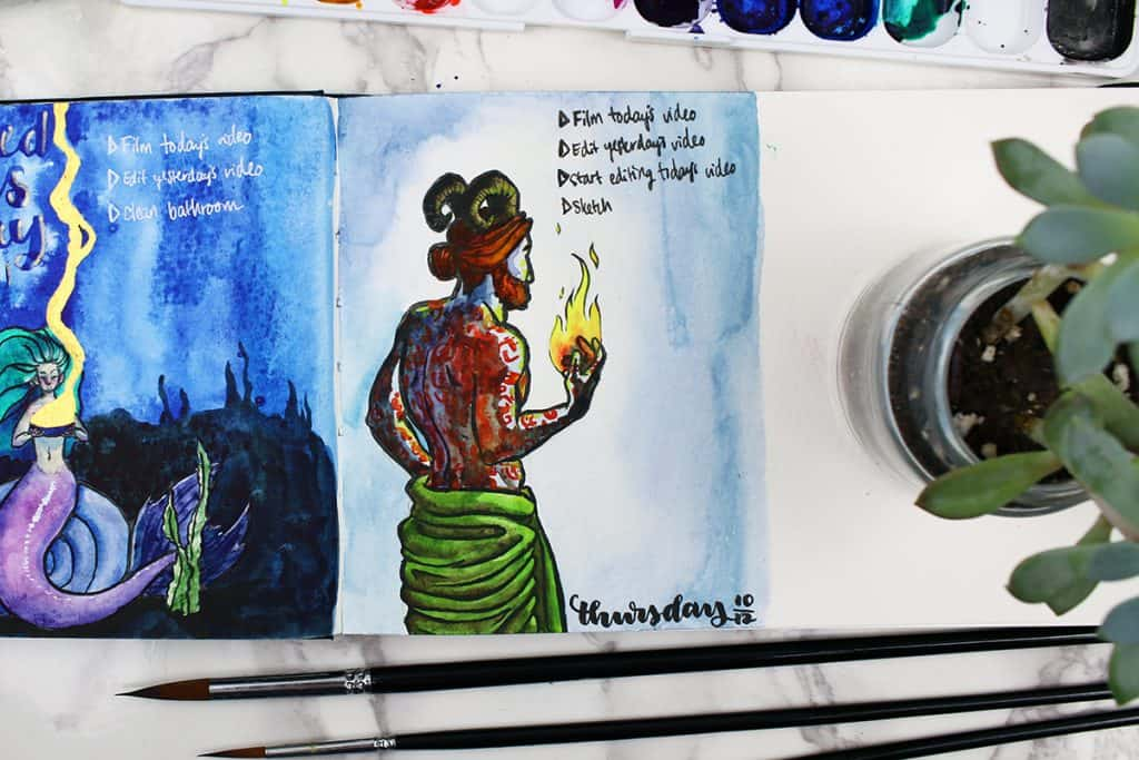 A daily spread in a watercolor bullet journal. A painting of a demon man, with horns and runes tattooed on his back. He is holding fire in his hand.