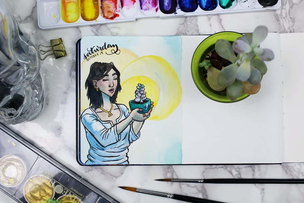 A daily spread in a watercolor bullet journal. This painting shows a young woman with a succulent in a planter, surrounded by golden light.