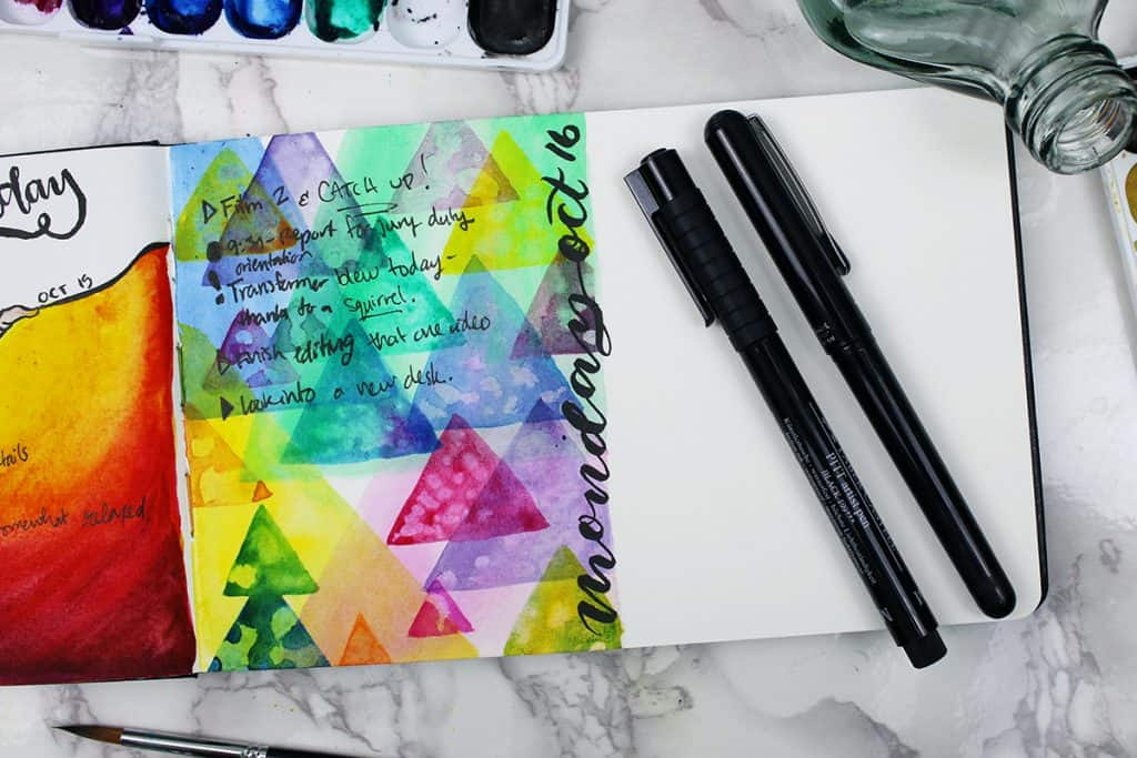 A daily spread in a watercolor bullet journal. This spread is more abstract, with several triangles in different colors overlapping each other.