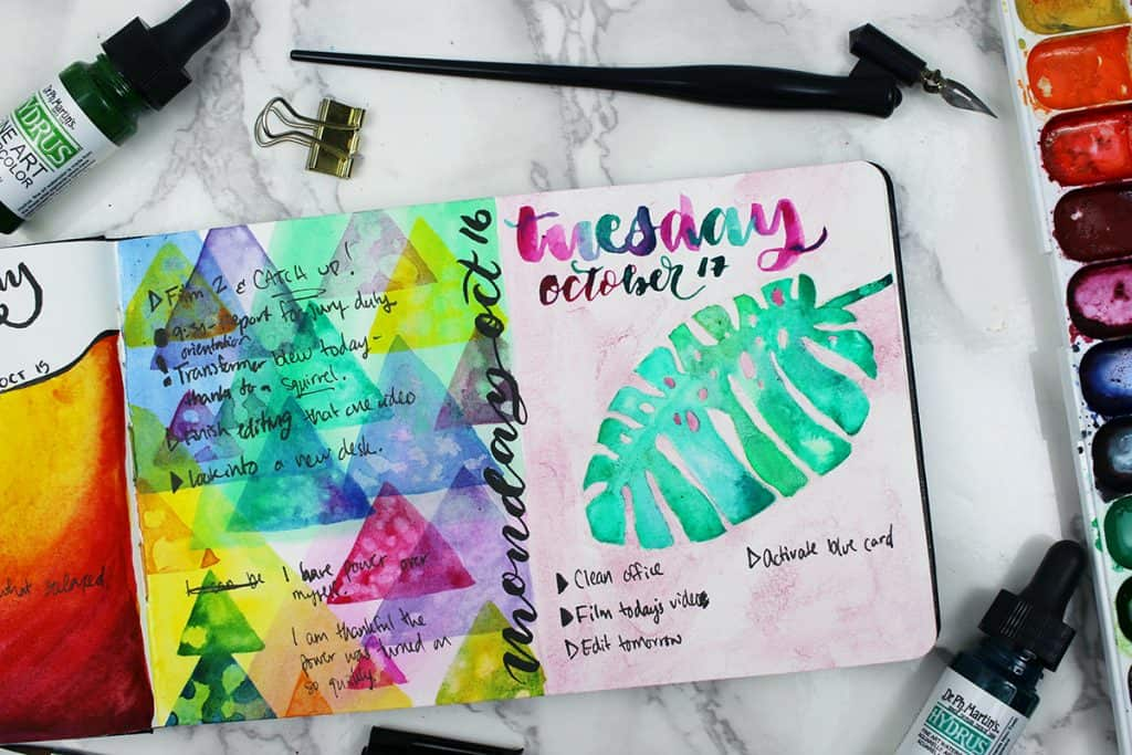 A watercolor bullet journal daily spread. This spread features a Monstera leaf painted over a pink background.