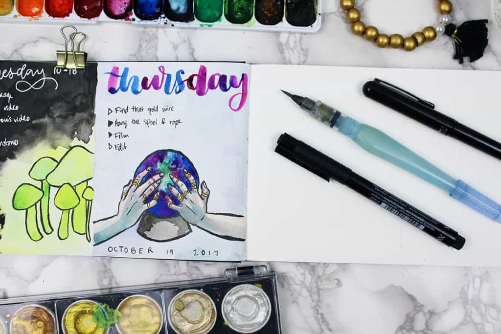 A daily watercolor bullet journal spread. This painting features a crystal ball being cradled by two bejeweled hands.