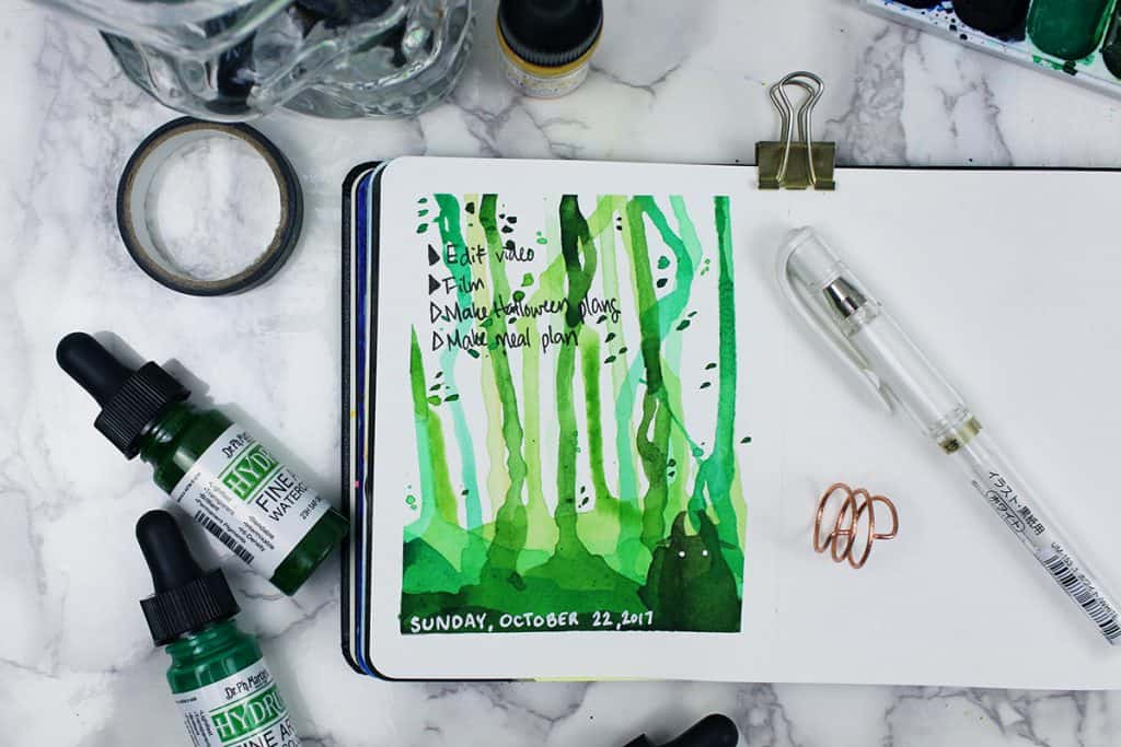 A daily spread in a watercolor bullet journal. The theme of this spread looks like a mystical forest, with a mysterious shadowy creature peering out from the bottom.