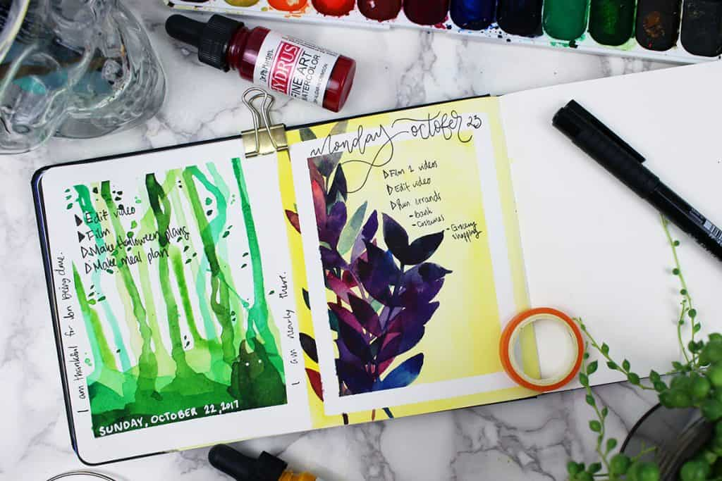 A watercolor bullet journal daily spread. This spread features dark purple and blue leaves against a bright yellow background. Washi tape was used to block the paint, creating a white border around the painting.