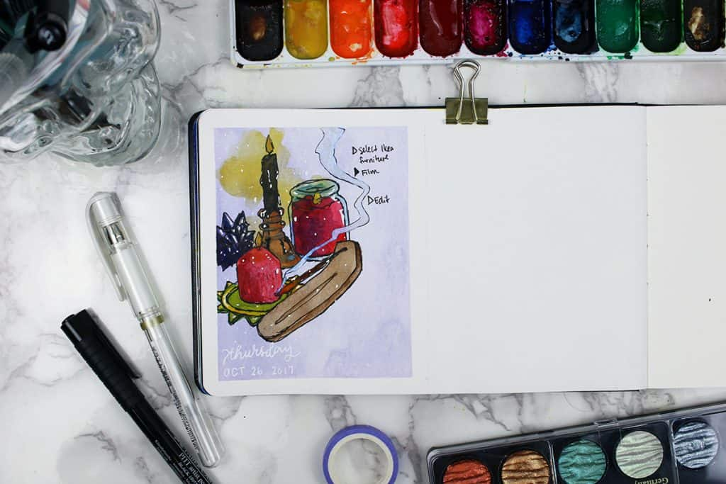 A daily spread in a watercolor bullet journal. This spread features two red candles, one black candle, a crystal, and an incense holder with a still-burning stick inserted.
