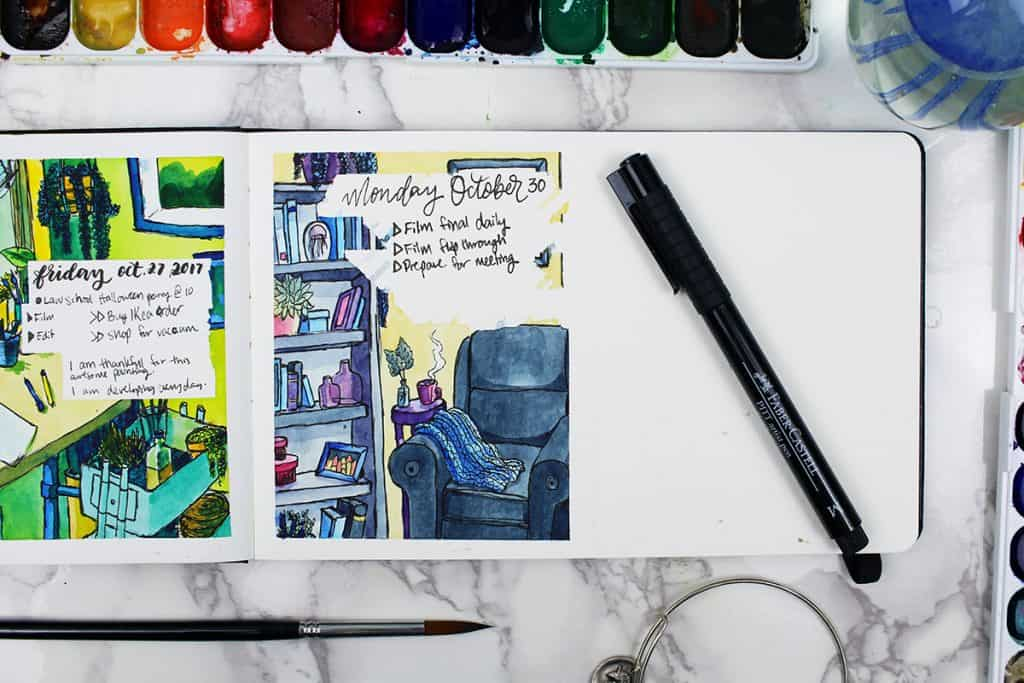 A daily watercolor bullet journal spread. This spread features a painting of a cozy reading nook.  A blue throw blanket rests on a comfy chair, sitting next to a bookshelf. A steaming mug of coffee sits on a table next to the chair.