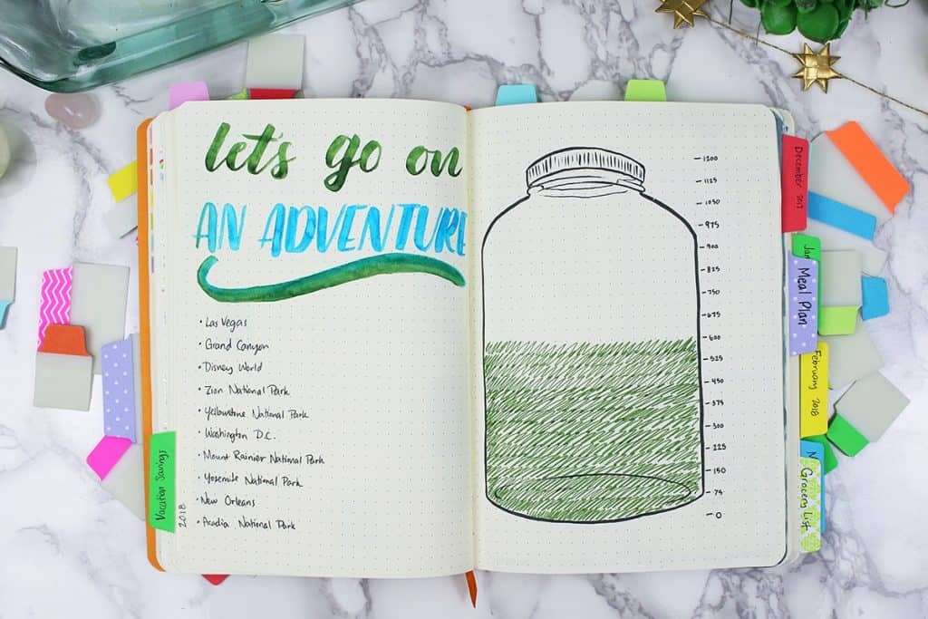 A savings tracker in a bullet journal, marked by a tab.