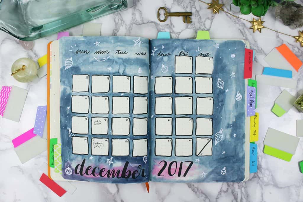 A bullet journal is open to a monthly spread that was created using watercolor paints and a black brush pen. The bullet journal is organized with colorful tabs on the side, marking different sections of the bullet journal.