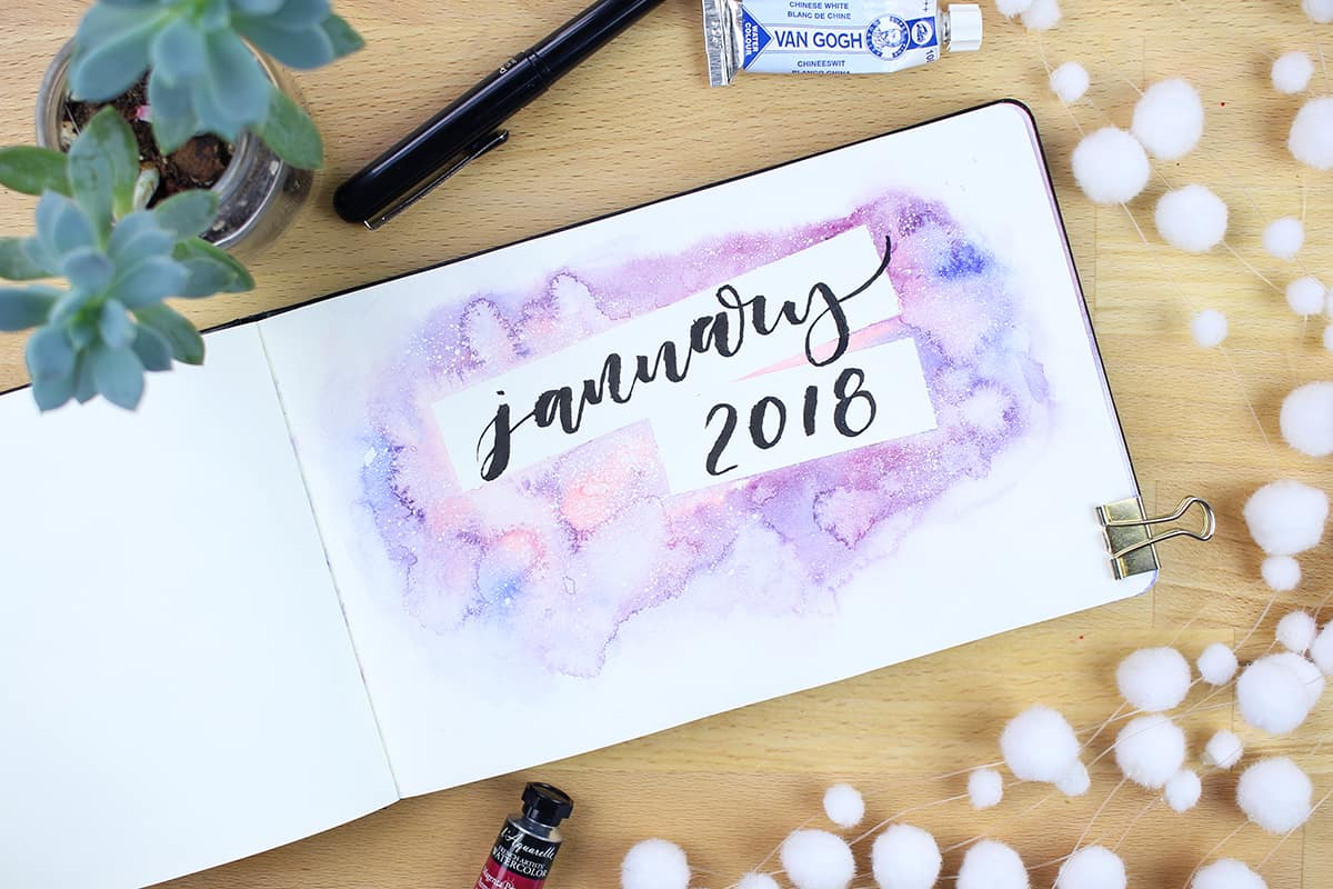 "A January cover page with a watercolor background and the word ""January"" lettered on it."