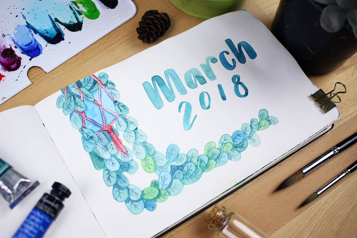 "A March Cover page with a painted hanging plant and the words ""March 2018"" written on the page."