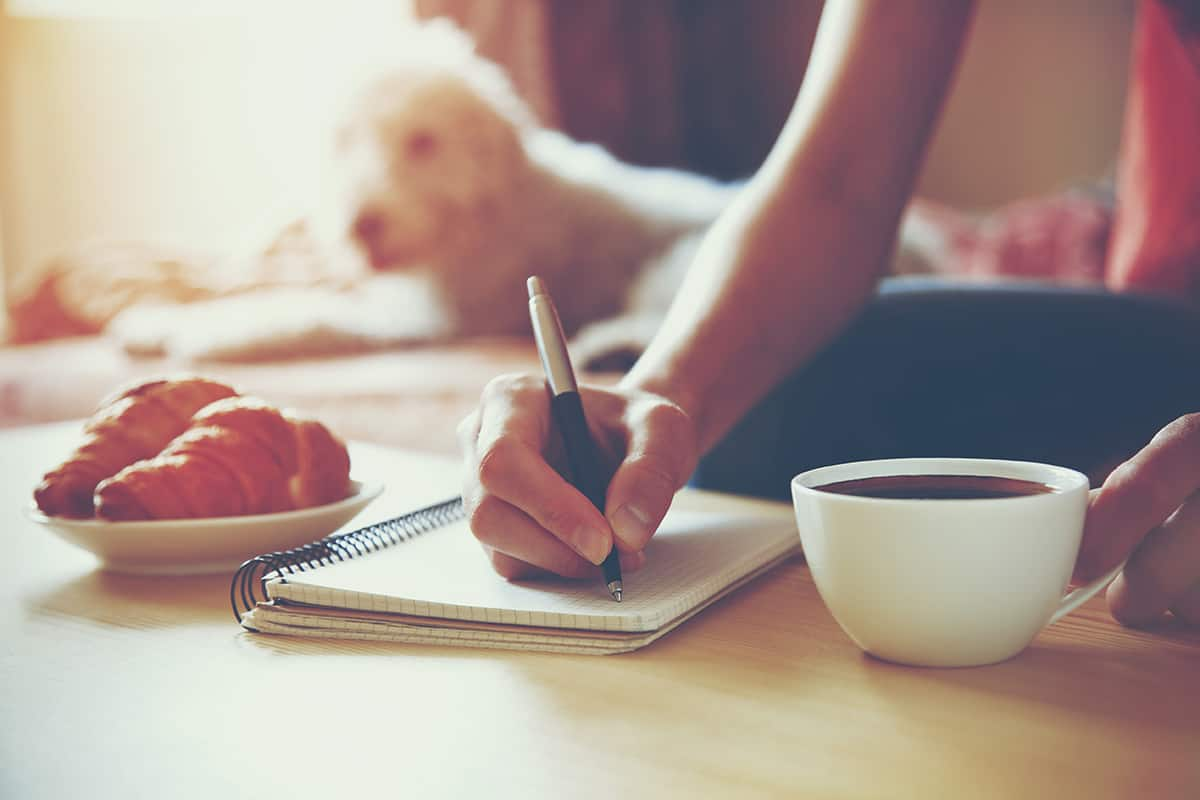 Girl writing in journal with coffee