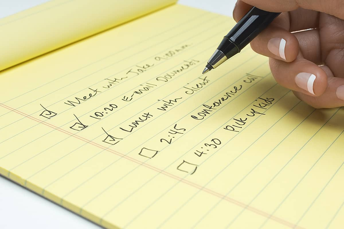 Closeup of female hand checking notepad with reminders written over white background