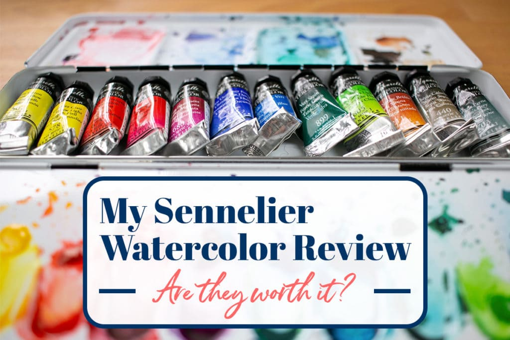 "Angled shot of the paint tubes in the center of the palette with splotches of used paint all over the palette, with a graphic containing ""My Sennelier Watercolor Review -- Are they worth it?"" imposed over it."