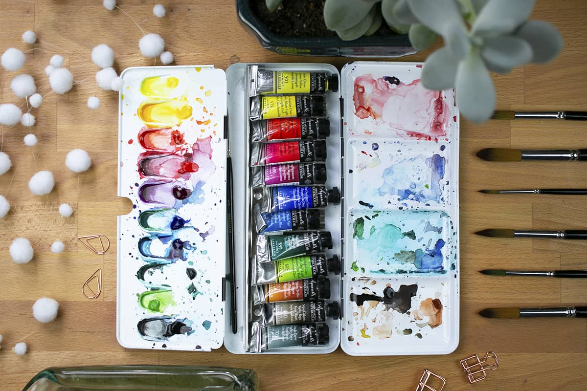 Overhead view of the messy open palette containing all the tubes of paint.
