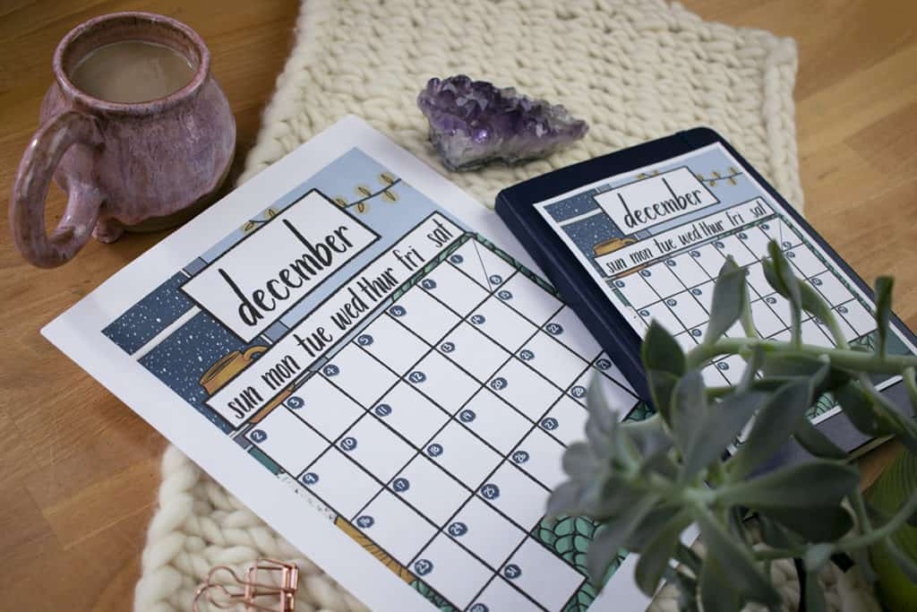 Close up angle shot of December 2018 Printable with coffee mug, succulent, and amethyst sitting nearby