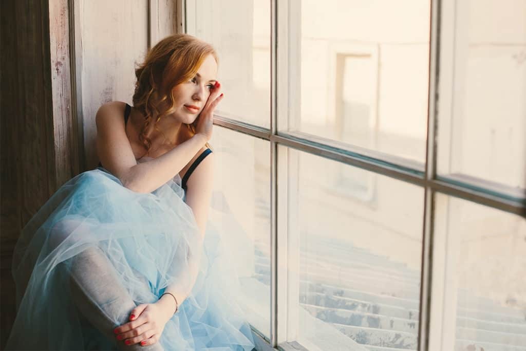 Toned portrait of a young woman with red hair and blue fluffy skirt near the big window
