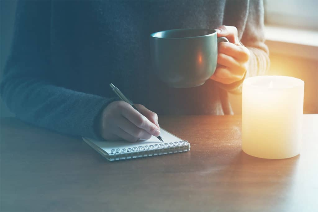 female hands with pen and cup of tea or coffee writing on notebook in candle light