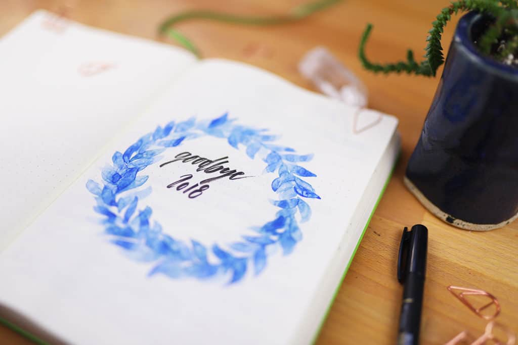 "Up close shot of blue watercolor wreath with ""Goodbye 2018"" lettered in the center."