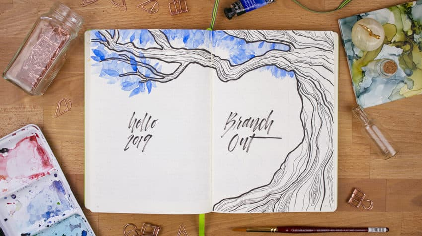 "Bird's eye view of a spread with an illustrated tree with blue watercolor leaves. The lettering on the left page reads ""Hello 2019"", and the lettering on the right reads ""Branch Out""."