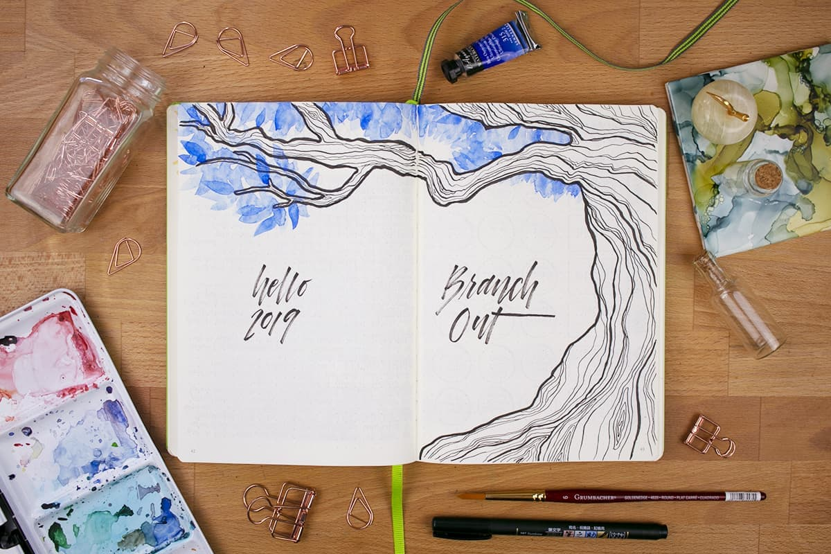 """Bird's eye view of a spread with an illustrated tree with blue watercolor leaves. The lettering on the left page reads """"Hello 2019"""", and the lettering on the right reads """"Branch Out""""."""
