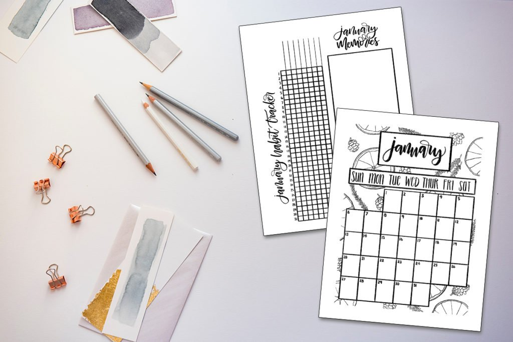 January calendar and tracker printables superimposed over a flatlay with pencils and watercolor samples.