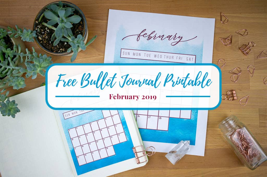 "Photo of two printables and a journal on a wooden desktop with graphic overlay saying, ""Free Bullet Journal Printable February 2019""."