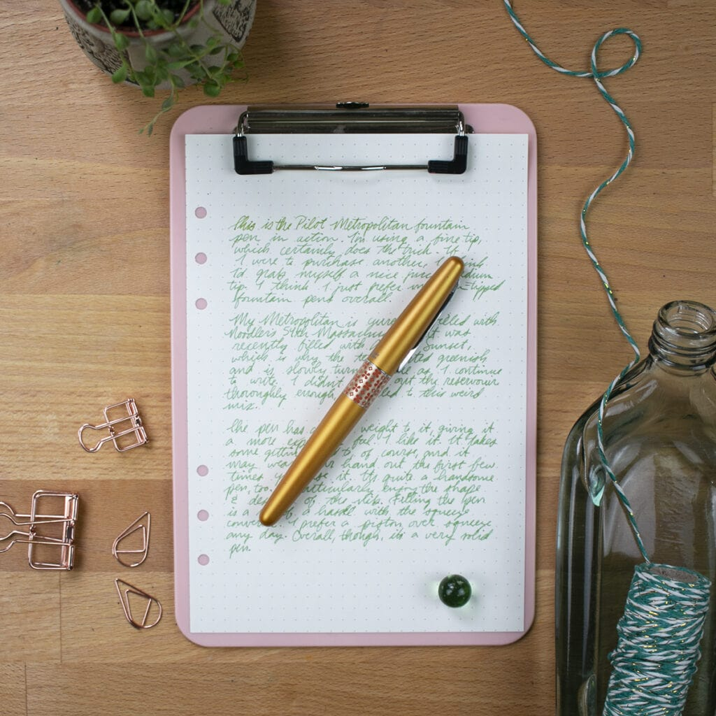 Overhead view of pen on clipboard with paper covered in green writing.